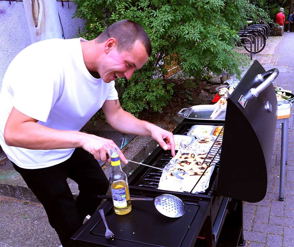 Ein junger Mann steht am Grill und bereitet lächelnd das Essen zu.