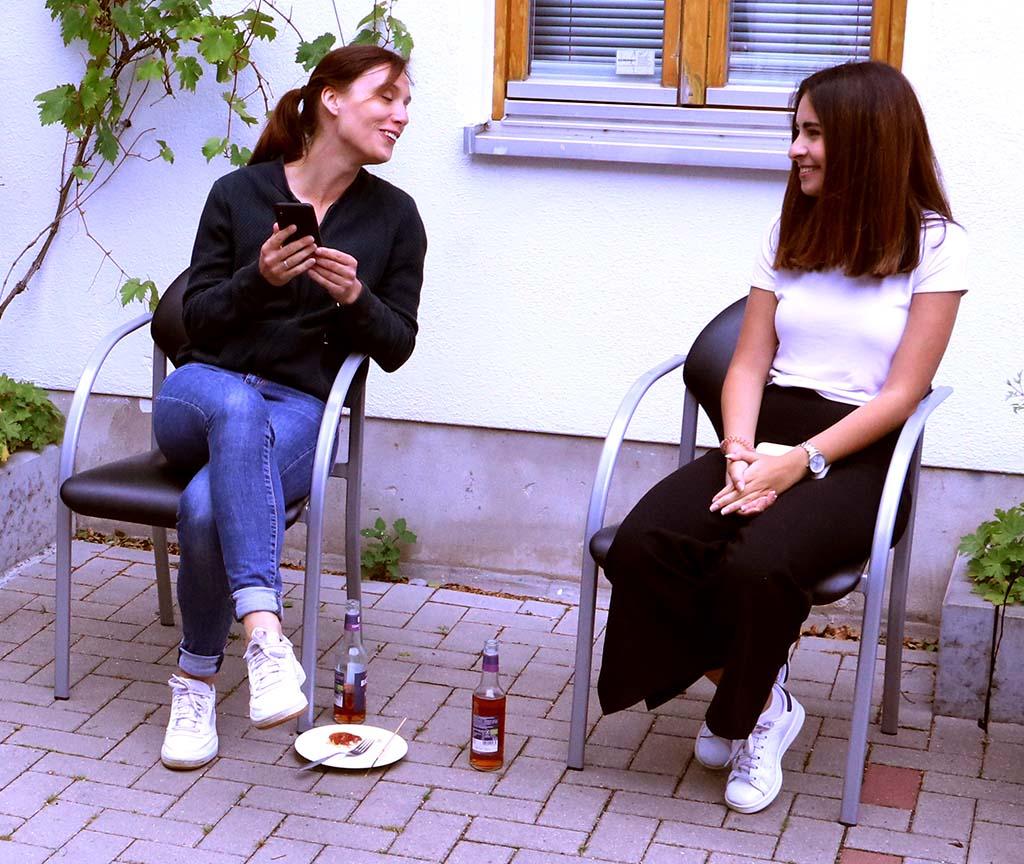 Zwei junge Frauen sind in ein Gespräch vertieft.