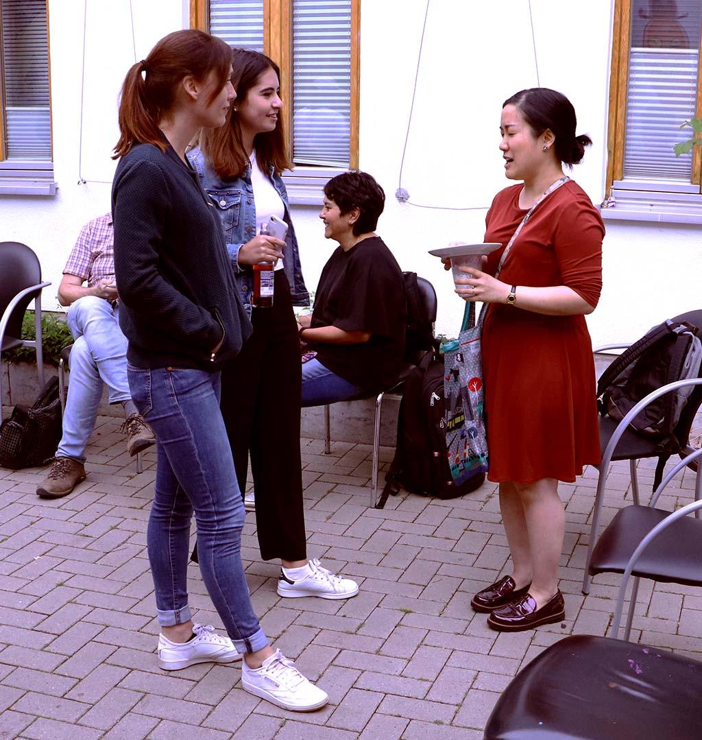 Drei Frauen reden im Stehen miteinander.