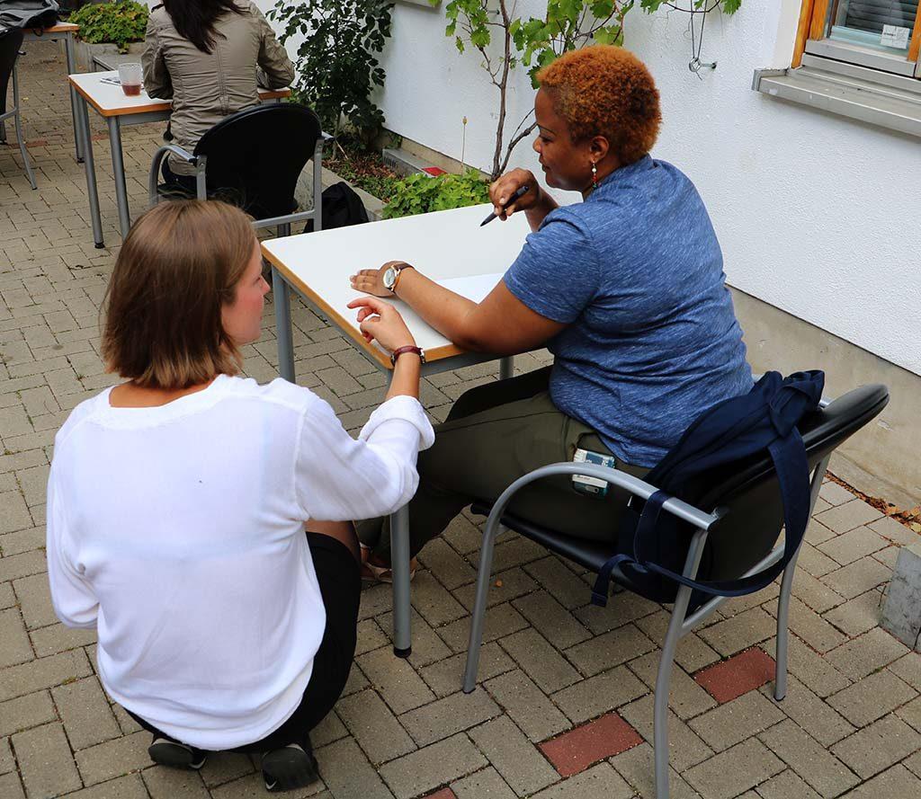 Die Gruppenleiterin kniet neben einer Teilnehmerin, die am Tisch sitzt und redet mit ihr.
