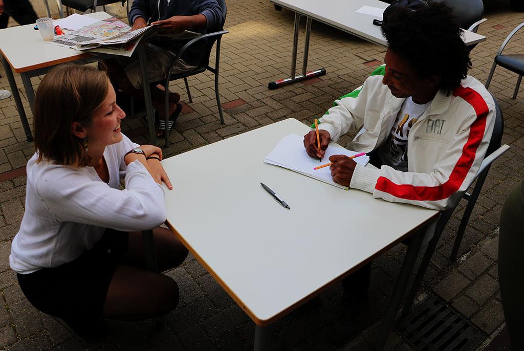 Die Gruppenleiterin kniet vor dem Tisch und spricht mit einem der Teilnehmer, der am Tisch sitzt.