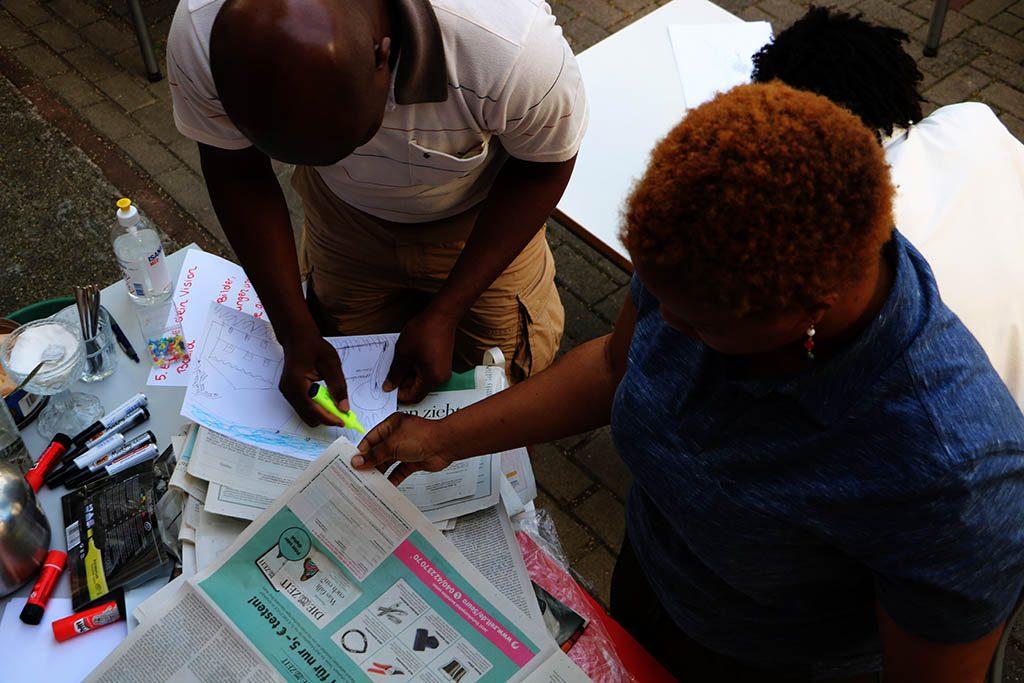 Ein Mann und eine Frau sind über eine Zeitung gebeugt.