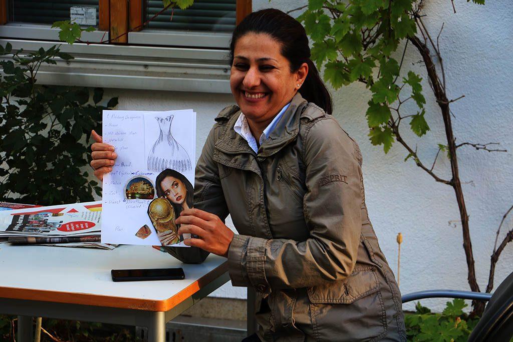 Eine Frau präsentiert breit lächelnd ihr Vision Board.