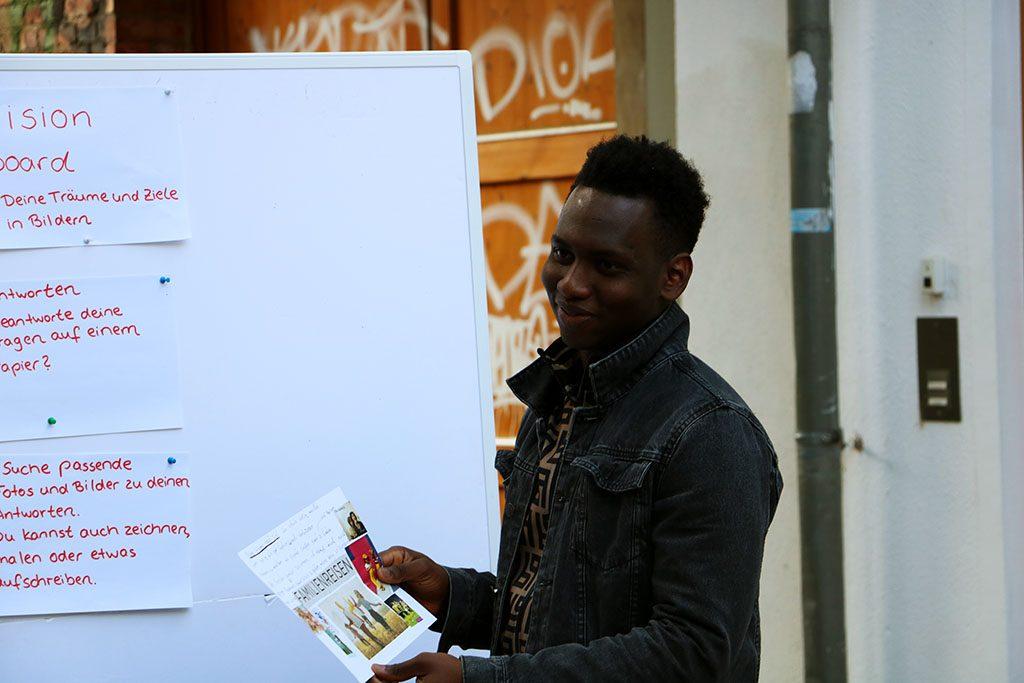 Ein junger Mann präsentiert sein Vision Board.