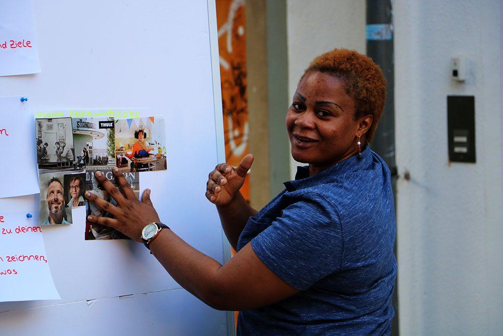 Eine Frau präsentiert ihr Vision Board lächelnd.
