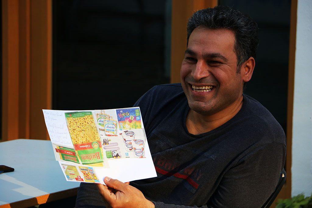 Ein Mann präsentiert lächelnd sein Vision Board.
