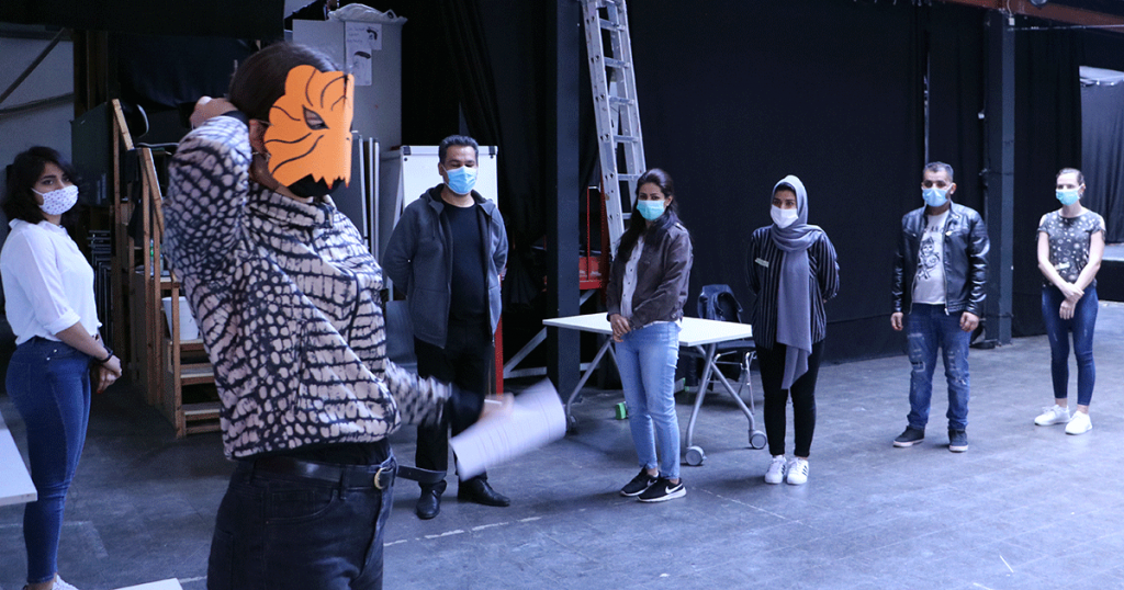 Die Gruppe trägt Masken und steht im Abstand zueinander. Die Gruppenleiterin trägt eine Tigermaske aus Papier.