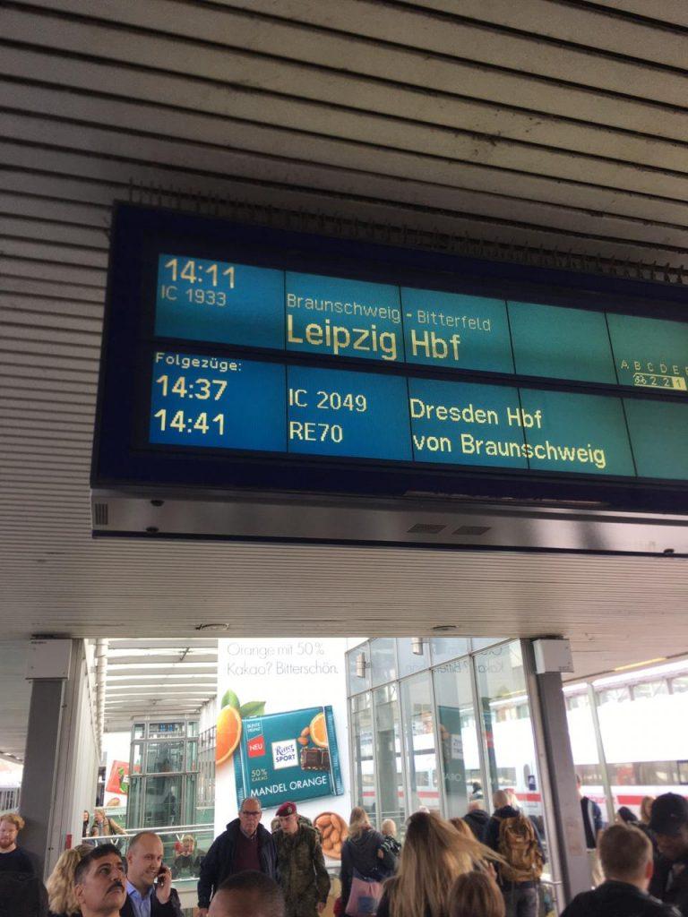 Das Schild am Bahnhof kündigt die Ankunft des Zugs nach Leipzig Hauptbahnhof an.