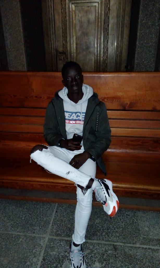 An junger Mann sitzt gelassen auf einer Bank.