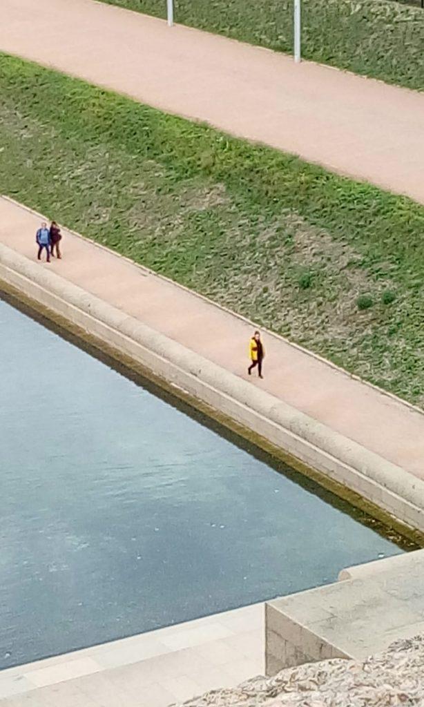 Eine Frau, gefolgt von einem Pärchen spazieren am Wasser entlang.