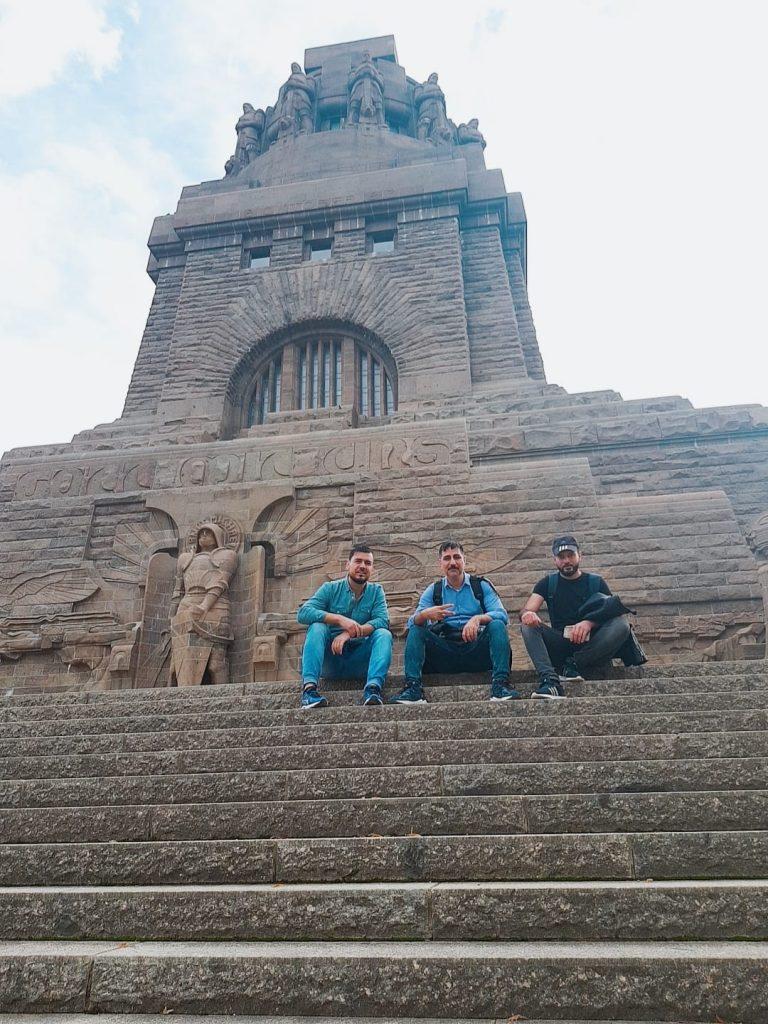 Drei Leute sitzen auf einer alten Treppe.