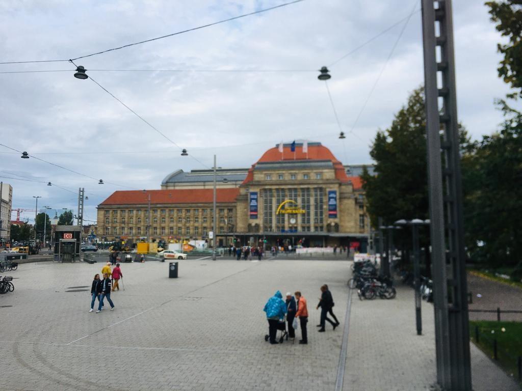 Ein sehr großer Platz in der Stadt, der bis auf kleine Grüppchen menschenleer ist.