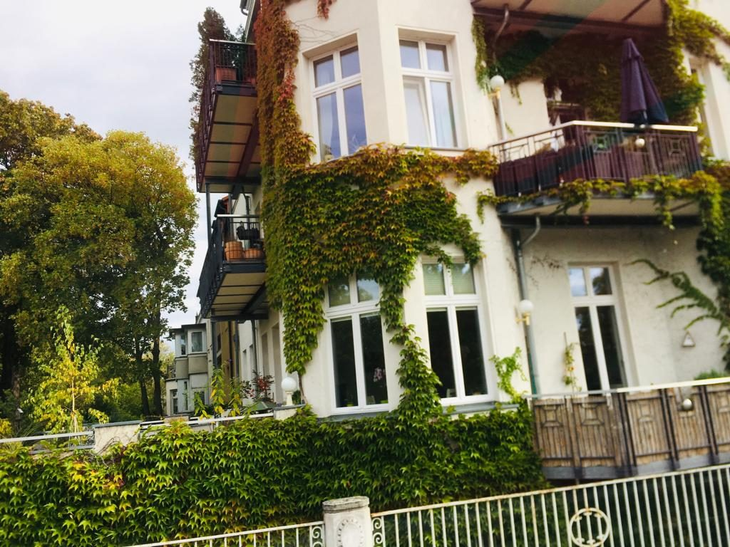 Ein feines Haus an dessen Fassade von Efeu bewachsen ist.