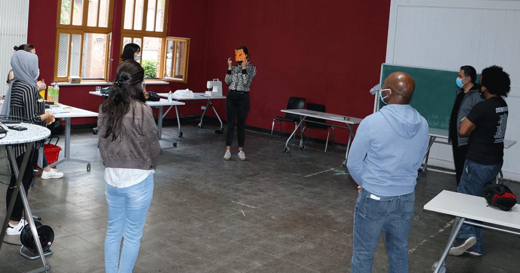 Die Gruppenleiterin erklärt den Teilnehmern Verhaltensregeln im Umgang mit dem Coronavirus.