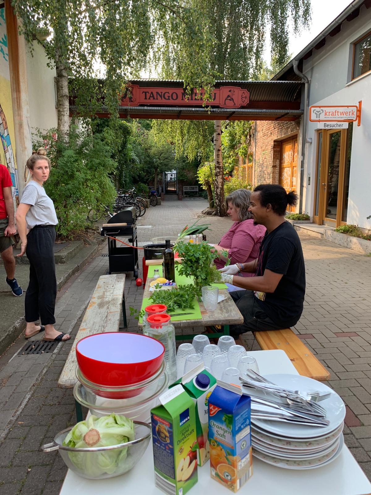 Auf einem Tisch wird draußen Essen zubereitet.