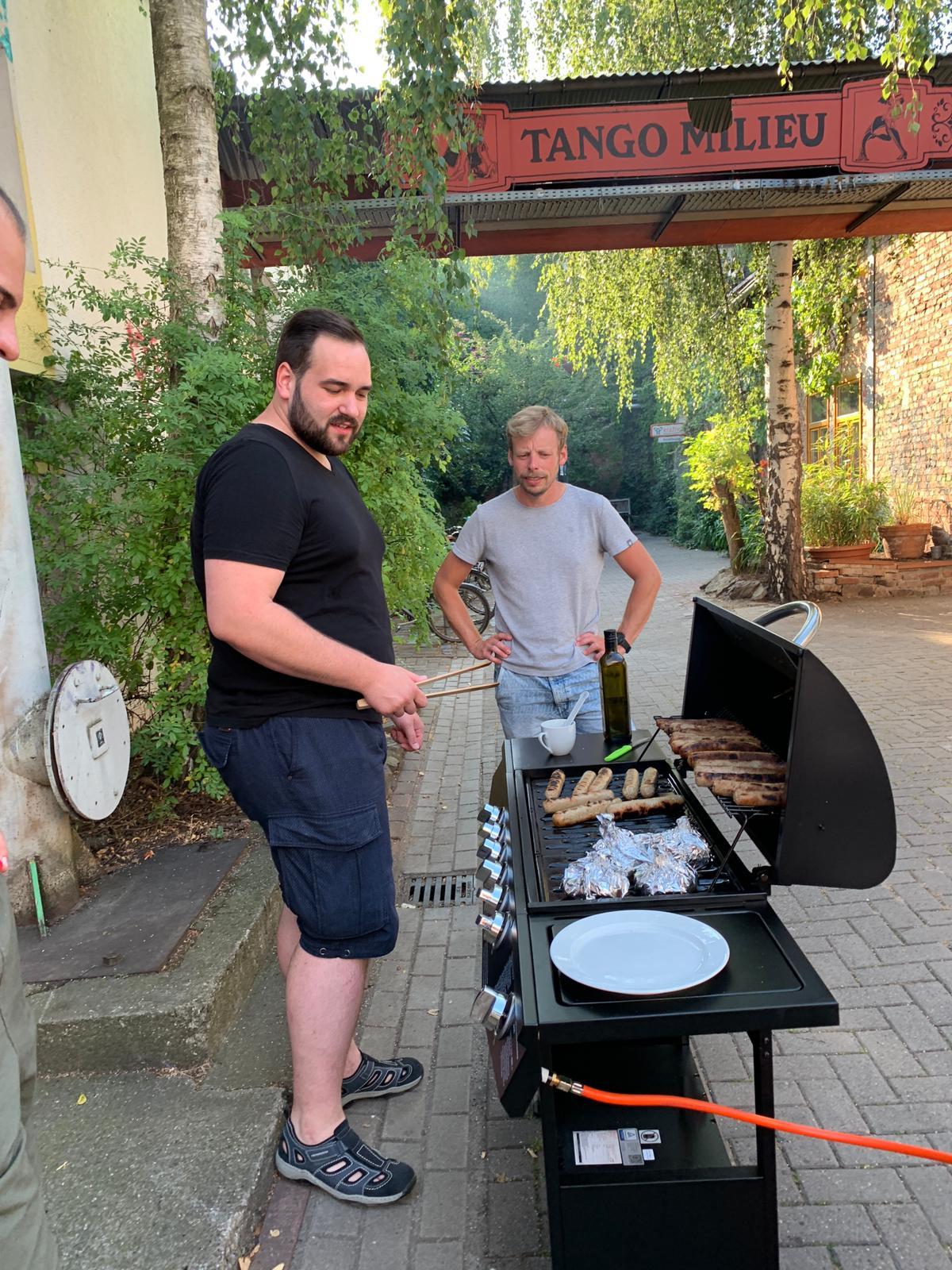 Zwei Männer stehen am Grill.