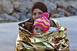 Eine Frau hält ein Kind und ist in wärmende Folie gewickelt.
