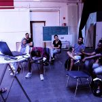 Die Gruppe sitzt auf Stühlen und lauscht einer Präsentation.