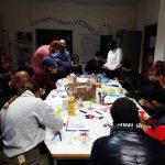 Die Gruppe sitzt an einem großen Tisch zusammen und ist in ein Projekt vertieft.