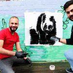 Zwei Männer tragen mit einer Schablone das Bild eines Pandabären auf eine Wand auf.