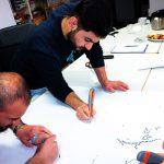 Zwei Männer schreiben auf Plakate.