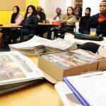 Die Gruppe sitzt an Tischen, auf einem Tisch liegen viele Zeitungen bereit.
