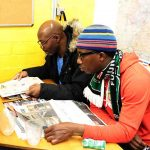 Zwei Männer haben Zeitungen aufgeschlagen und lesen.