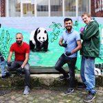 Drei Männer posieren vor dem Bild eines Pandabären für ein Foto.