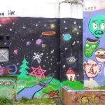 Eine bunt bemalte Wand geschmückt mit einem Sternenhimmel, grünen Landschaften und Gesichtern.