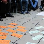 Die Gruppen schaut auf dem Boden ausgebreitete Zettel an.