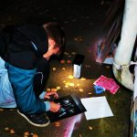 Im Dunkeln, erleuchtet von einer Laterne, sprüht ein Mann ein Symbol auf ein Plakat.