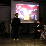Die Gruppenleiterin erzählt etwas, im Hintergrund läuft der Projektor.