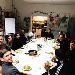 Die Gruppe sitzt an einem frisch gedeckten Essenstisch und posiert vor dem Essen für ein Gruppenfoto.