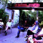 Die Gruppe ist draußen in einem Sitzkreis versammelt und diskutiert.