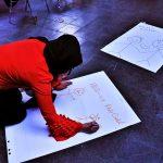 Eine Frau schreibt auf ein Plakat.