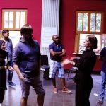 Die Gruppenleiterin führt mit einem Assistenten zusammen etwas vor.